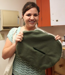 Intern Victoria holds a pouch that is designed to mimic the pouch of a marsupial. The fabric is extremely soft and keeps the baby warm.  The pouch is also seamless to prevent the newborn from ingesting any loose fabric.