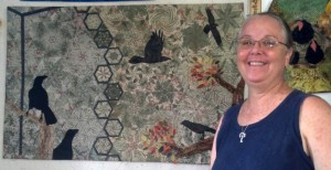 Alsyon stands in front of a quilt she made, inspired by the alala's hoped-for return to the wild.