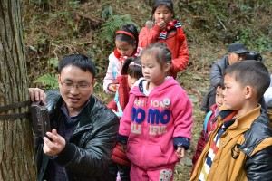 Fanjingshan nature reserve biologist Lei Si showed children how to mount a camera trap on a tree. (Photo by Kefeng Niu)