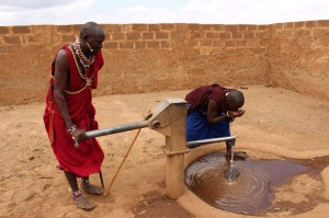 Two maasai warriors get some refreshment by the new water pump near their boma just outside Ambsolei National Park, surrounded by a wall to protect against elephant damage.